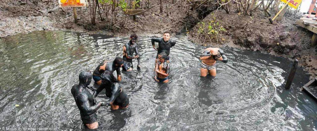 Pessoas tomando banho de lama no centro de um manguezal.