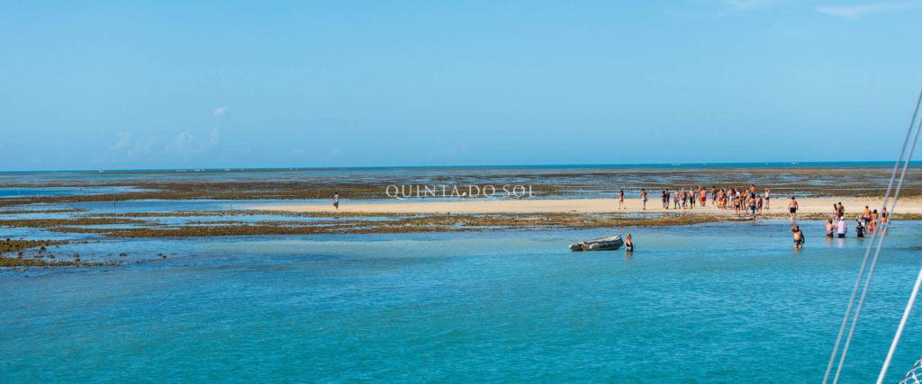 Vista horizontal do mar, região de areia com turistas. Céu azul e ensolarado.