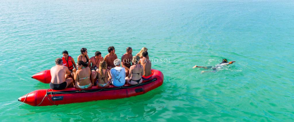 Doze pessoas a bordo de uma balça em pleno mar. Um banhista praticando mergulho ao lado.
