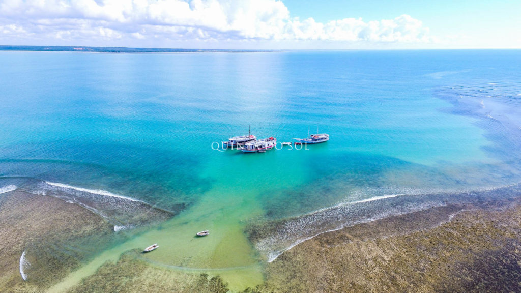 Três barcos de navegação em meio ao mar aberto. Céu ensolarado e azul celeste.