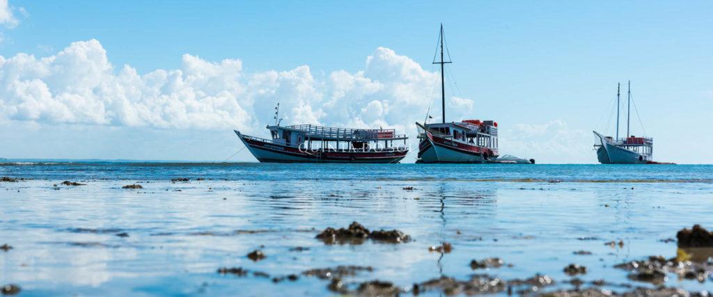 Céu limpo e azul claro. Ao mar, três barcos fotografados de frente.